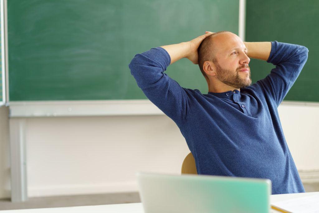 Lehrer vor Tafel mit Laptop ZDB