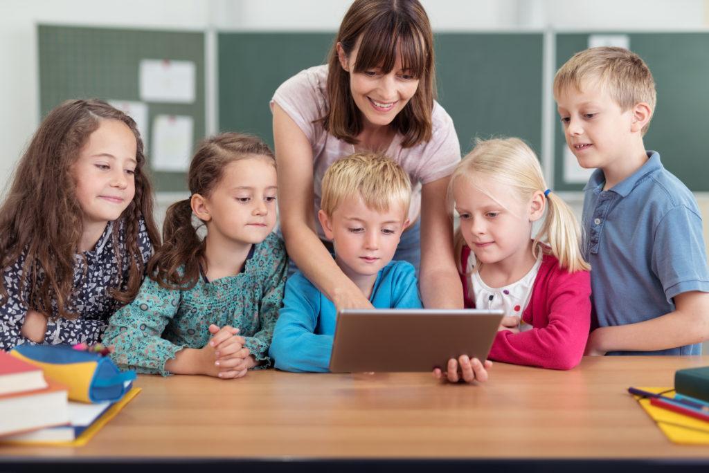 Lehrerin mit Kindern zeigt auf ein Tablet ZDB