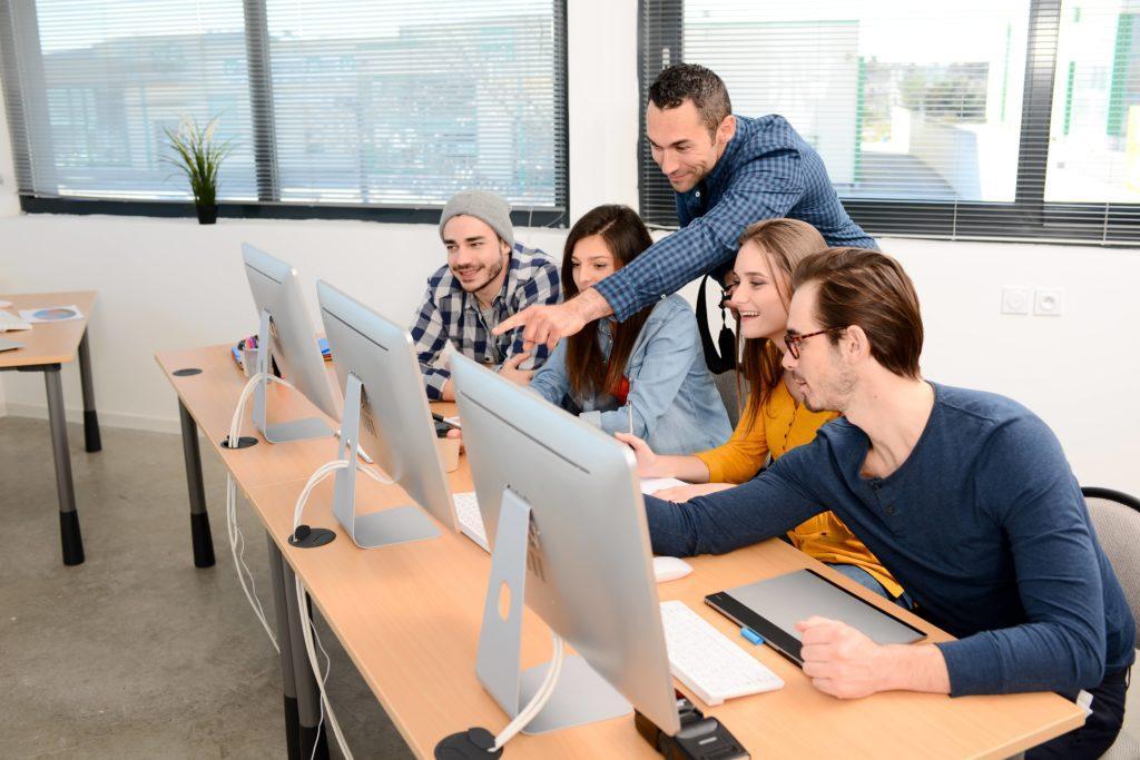 Digitales Classroom Management Lehrer und Gruppe an Jugendlichen vor PCs ZDB