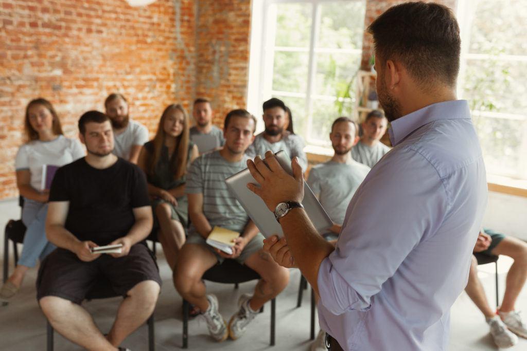 Mann zeigt einer Gruppe sitzender Personen etwas auf einem Tablet ZDB